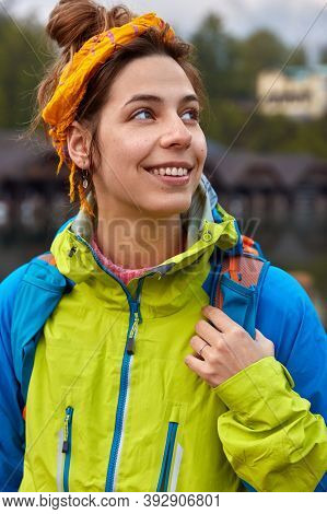 Vertical Shot Of Positive Caucasian Woman Looks Away, Strolls And Breathes Fresh Air, Wears Yellow H