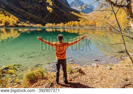 Happy Man At The Crystal Lake In Autumnal Mountains. Mountain Lake And Hiker Traveller