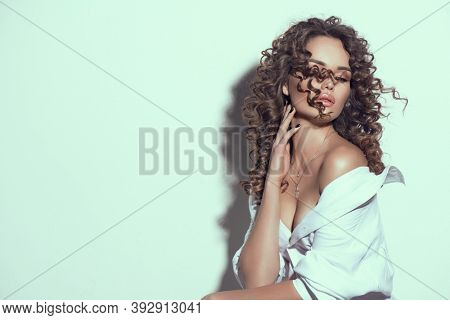 Beautiful young woman with curly hair posing, beauty model portrait, closeup. Beautiful sexy model girl in white cotton shirt. Flying hair, perfect make-up and manicure. Hairstyle.