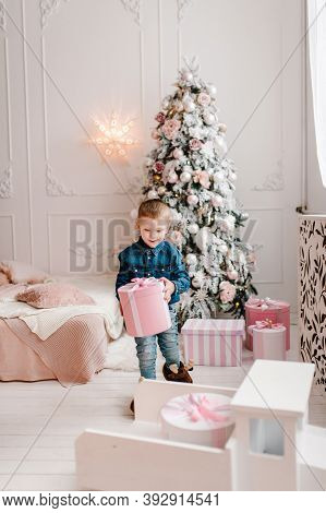 The Boy With Presents, Gifts Near Christmas Tree. Happy New Year And Merry Christmas. Christmas Deco
