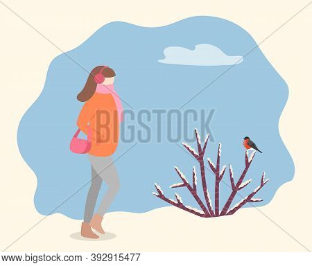 Woman Wearing Warm Winter Jacket And Carrying Handbag Walking In Forest Or Park. Female Passing Bush