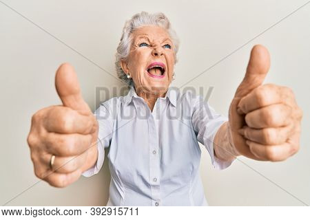 Senior grey-haired woman doing thumbs up positive gesture angry and mad screaming frustrated and furious, shouting with anger looking up.