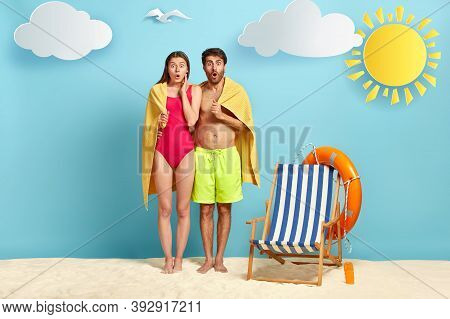 Terrified Lovers Stand Closely, Covered With Soft Towel, Stand On Tropical Beach, Stare With Widely
