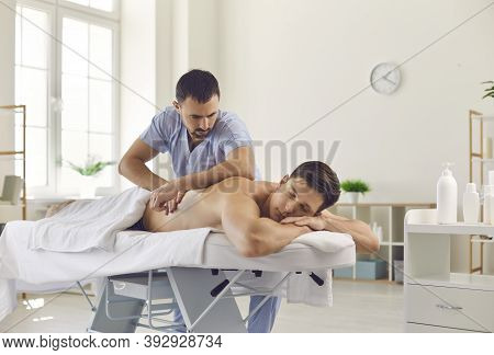 Man Chiropractor Making Acupressure, Manual Therapy Or Rehabilitation Massage