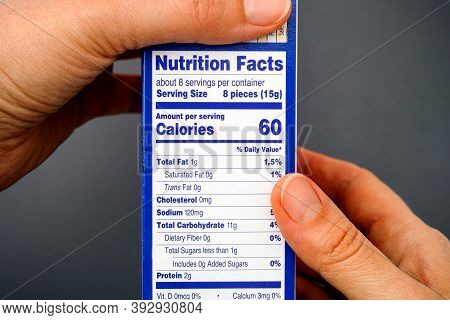 Nutrition Facts On Food Box In Woman Hands. Gray Background.