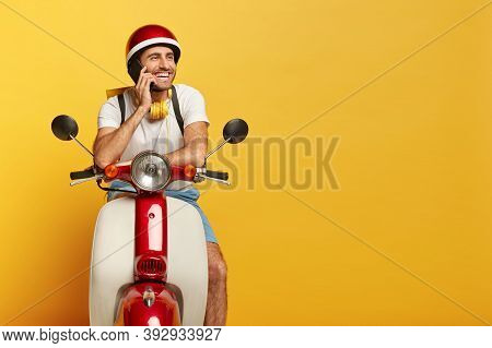 Happy Man Courier Poses On Fast Motorbike, Talks Via Cell Phone During Rest, Carries Rucksack, Wears