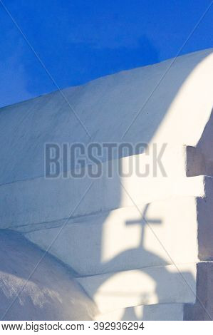 Vertical Shot, Beautiful Greek Chapel. Holiday Destination Of Ios Island.  Shadows Cast On The White