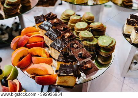 Plate With Fruit. Decorated Dessert Table For A Party: Cakes, Sweets, Fruits And Goodies. Delicious