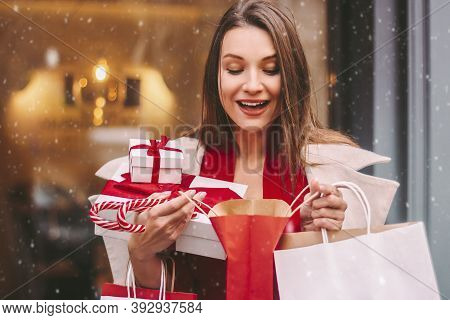 Happy Beautiful Excited Girl Look Into Shopping Bag And Smile On Snowy Winter Street. Cheerful Young
