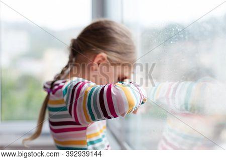 Sad Child Looking Through Window Durin Rain. Upset Kid In Self Isolation At Home During Lockdown. Li