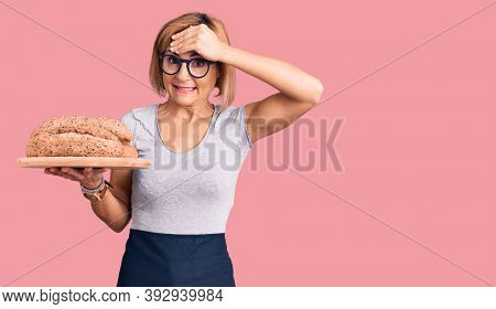 Young blonde woman holding wholemeal bread stressed and frustrated with hand on head, surprised and angry face