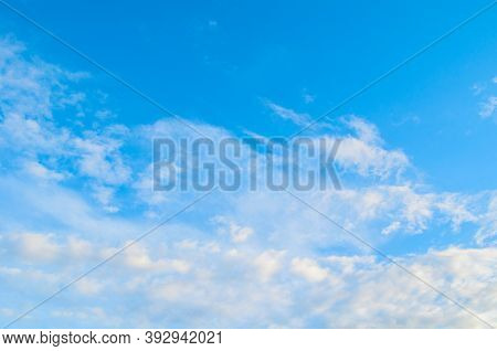 Blue sky background, white dramatic fluffy clouds lit by sunset light. Blue sky view, sunset sky background. Sky landscape, colorful sky view, sky background