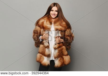 Beautiful Lady In A Luxury Elegant Fur Coat, Isolated In The Background. Model Girl Posing In Eco-fu