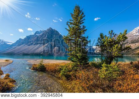 Majestic Rocky Mountains of Canada. Alberta. Glacial lake with azure clear water. Spruce and pines trees around the lake. The sun is reflected in the Lake Bow
