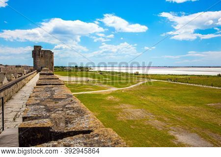 The port city of Aigues-Mortes. Salt mines. Salt development. Antique walls and picturesque powerful gates surround the ancient city. Around the walls are green lawns