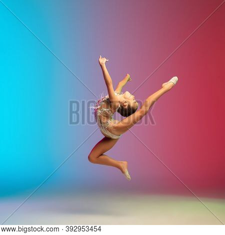 High Jump. Little Caucasian Girl, Rhytmic Gymnast Training, Performing Isolated On Gradient Blue-red