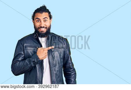 Young arab man wearing casual leather jacket pointing aside worried and nervous with forefinger, concerned and surprised expression