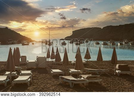 Empty Deckchairs On The Cala Vadella Beach In Ibiza Island During Beautiful Right Sunset, Moored Lux