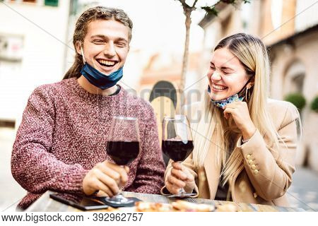 Young Couple In Love With Open Face Masks Having Fun At Wine Bar Outdoors - Happy Millenial Lovers E