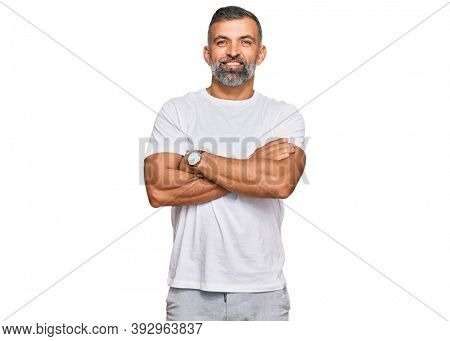 Middle age handsome man wearing casual white tshirt happy face smiling with crossed arms looking at the camera. positive person.