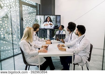 Team Of Five Multiethnical Doctors Having Video Conference Meeting In Hospital With Their Young Afri
