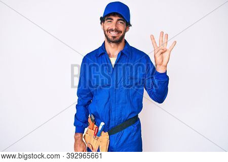 Handsome young man with curly hair and bear weaing handyman uniform showing and pointing up with fingers number four while smiling confident and happy.