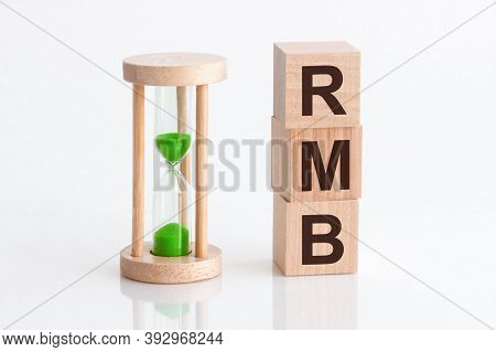 Close-up Of An Hourglass Next To Wooden Blocks With The Text Rmb