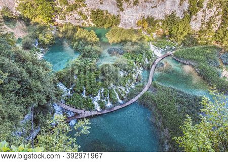 Top Summer View Of Plitvice Lakes With Waterfalls With Crystal Clear Water In Surrounding Forest In