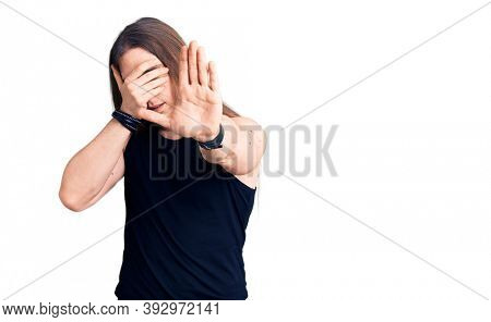 Young adult man with long hair wearing goth style with black clothes covering eyes with hands and doing stop gesture with sad and fear expression. embarrassed and negative concept.