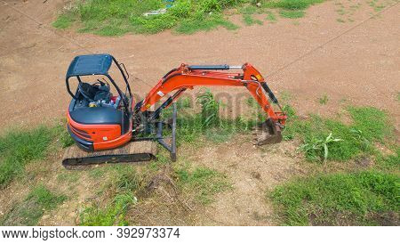 Aerial View Of Construction Tractor Car, Bulldozer, Or Backhoe Digging Road Or Street In Transportat