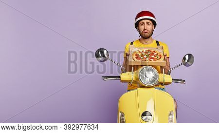 Photo Of Mournful Pizza Man, Has Dissatisfied Expression, Holds Cardboard Container With Tasty Fast