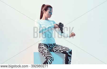 Athletic Young Brunette Female Massaging Hand By Handheld Percussion Massager In Neon Light