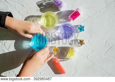 Child Holding Ingredients, Bottles, Jars For Making A Popular Childrens Toy From Glue. Homemade Pink