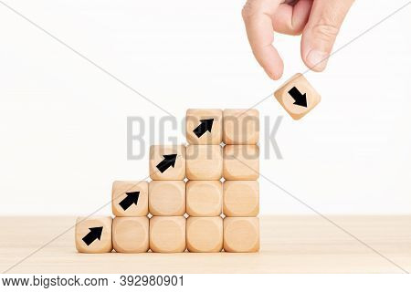 Hand And Wooden Block With Falling Arrow. Stock Market Collapse Or Financial Economy Crisis Concept.