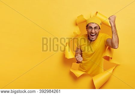 Joyous Cheering Guy Clenches Fists With Triumph, Happy Win Game, Has Successful Day, Wears Yellow Ou