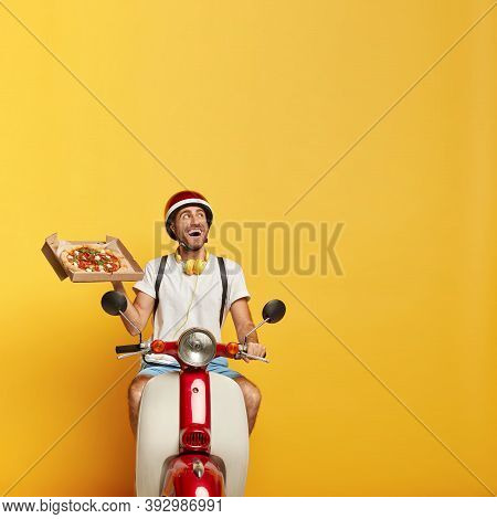 Punctual Smiling Young Pizza Delivery Driver Focused Upwards With Happy Look, Holds Cardboard Contai