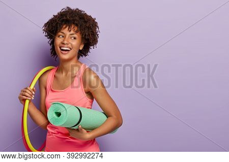 Fitness Woman With Dark Skin, Works With Hula Hoops, Holds Rolled Karemat For Training, Laughs Joyfu