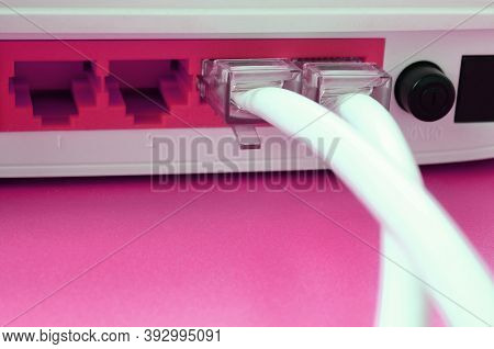 The Internet Cable Plugs Are Connected To The Internet Router, Which Lies On A Bright Pink Backgroun