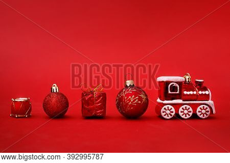 Toy Train With Christmas Decoration On A Red Background. Christmas Greeting Card Concept. Minimalism