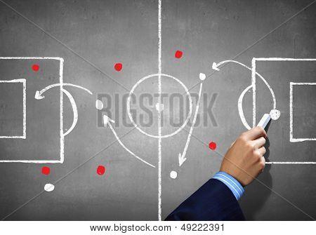 Close up image of human hand drawing football tactic plan