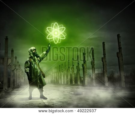 Image of man in gas mask and protective uniform touching atom sign poster