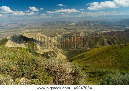 Saimaly-Tash valley with mountains on horizon and blue sky with cloud
