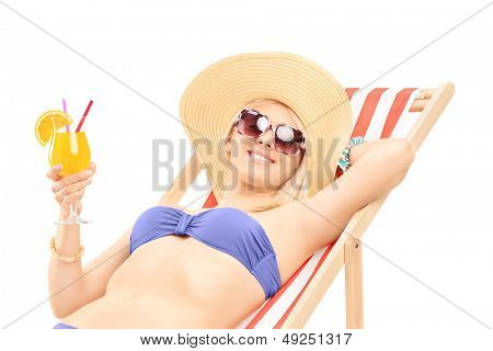 Smiling young woman sunbathing and holding a cocktail, isolated on white background