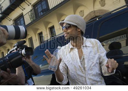 Male celebrity being interviewed by paparazzi