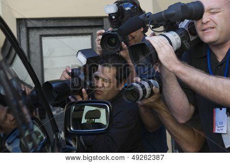 Closeup of paparazzi photographers at car window