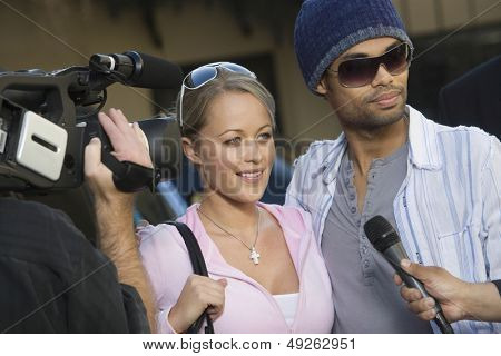 Closeup of celebrity couple being interviewed by the media