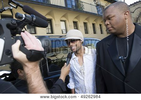 Male celebrity with bodyguard being interviewed by paparazzi