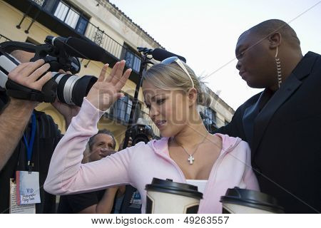 Closeup of a female celebrity and paparazzi