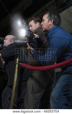 Side view of photographers across rope barrier at media event