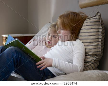 Side view of two young sisters reading book on a bed